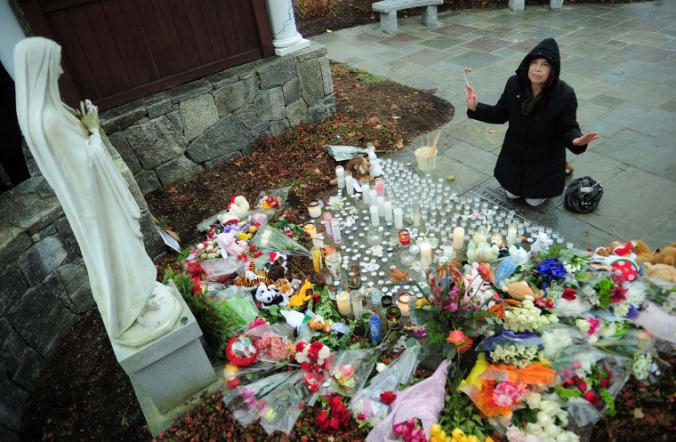 A parishioner pays her respect at makeshift altar to the victims of an elementary school shooting after attending Sunday's Mass at St Rose of Lima Church in Newtown, Connecticut, December 16, 2012. (Emmanuel Dunand/AFP/Getty Images)