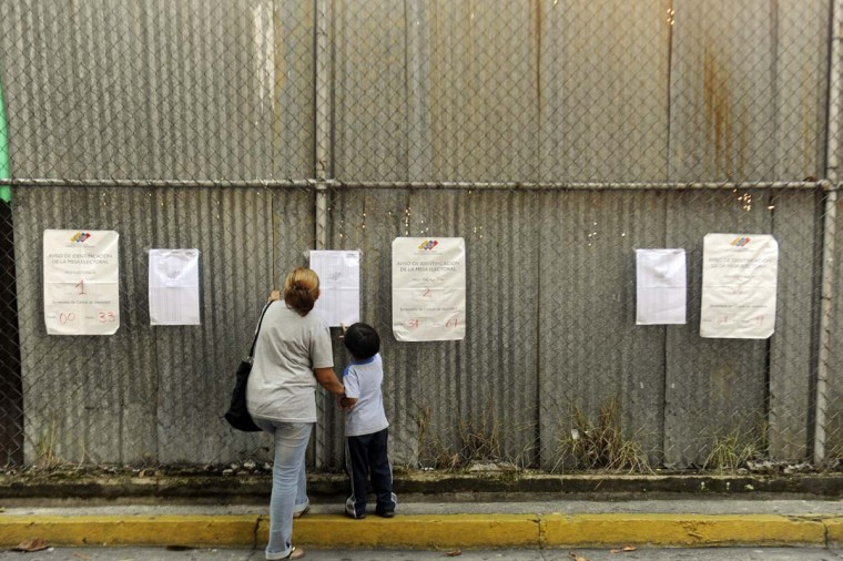A woman checks an electoral roll before casting her vote at a polling station in Caracas, Venezuela during state elections on December 16, 2012. (Leo Ramirez/AFP/Getty Images