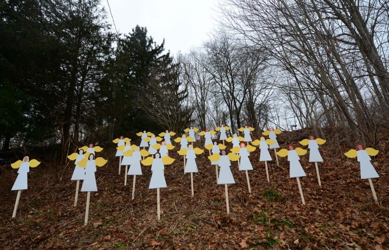 Twenty-seven angel wood cut-outs are set up on hillside in memory to the victims of an elementary school shooting in Newtown, Connecticut, December 16, 2012. Twenty-six people were shot dead, including twenty children, after a gunman identified as Adam Lanza opened fire at Sandy Hook Elementary School. (Emmanuel Dunand/AFP/Getty Images)
