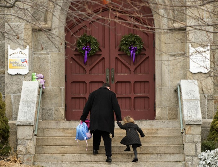 A man helps a little girl up the steps of Trinity Church December 16, 2012 in Newtown, Connecticut. The people of Newtown, soon to be joined by President Barack Obama, poured into churches Sunday to pray for the 20 children and seven adults slaughtered in one of the worst ever US shooting massacres. The small Connecticut town led the nation in mourning 48 hours after Adam Lanza burst into Sandy Hook Elementary School and murdered two roomfuls of six- and seven-year-old children, the school principal and five other female staff. From early Sunday churches filled and the town Christmas tree became an impromptu place of remembrance, with people pausing every few minutes to pray and cross themselves under a light snowfall. (Don Emmerton/Getty Images)