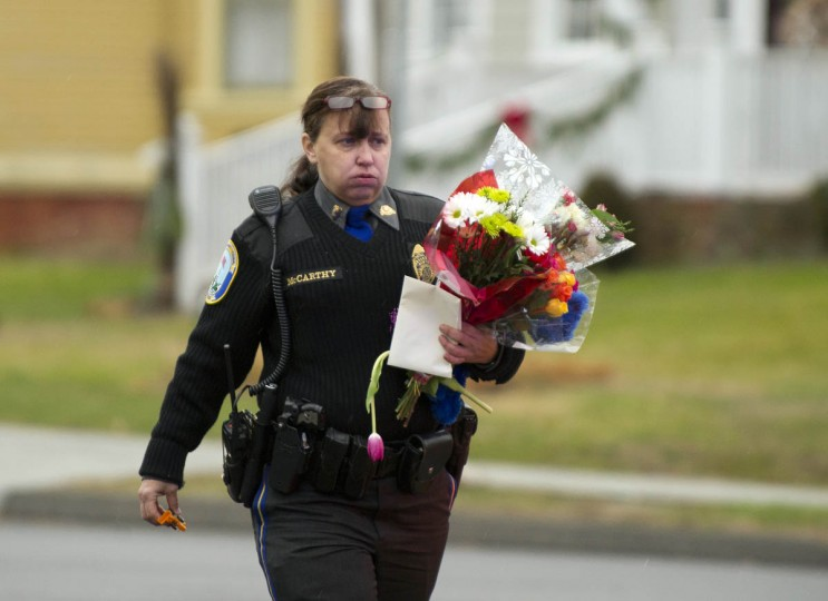 A police officer removes flowers from a busy intersection December 16, 2012 in Newtown, Connecticut, which they said they were afraid the memorial, left for the Sandy Hook Elementary school victims, may cause a traffic hazard. The people of Newtown, soon to be joined by President Barack Obama, poured into churches Sunday to pray for the 20 children and seven adults slaughtered in one of the worst ever US shooting massacres. The small Connecticut town led the nation in mourning 48 hours after Adam Lanza burst into Sandy Hook Elementary School and murdered two roomfuls of six- and seven-year-old children, the school principal and five other female staff. From early Sunday churches filled and the town Christmas tree became an impromptu place of remembrance, with people pausing every few minutes to pray and cross themselves under a light snowfall. (Don Emmert/Getty Images)