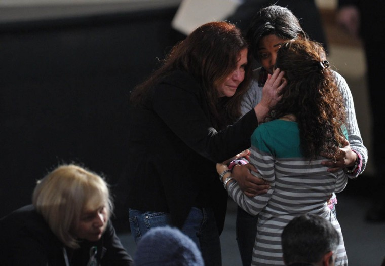 People comfort each other at a memorial service for the victims and relatives of the Sandy Hook Elementary School shooting on December 16, 2012 in Newtown, Connecticut. US President Barack Obama will address the memorial for the twenty-six people, 20 of them children, who were killed when a gunman entered Sandy Hook Elementary and began a shooting spree. (Mandel Ngan/Getty Images)