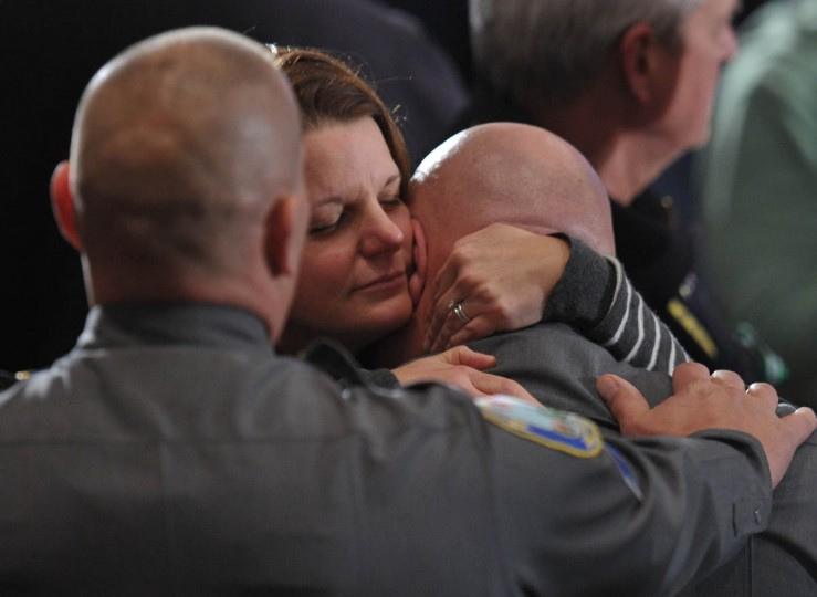 A woman comforts a member of the Newtown police at a memorial service for the victims and relatives of the Sandy Hook Elementary School shooting on December 16, 2012 in Newtown, Connecticut. US President Barack Obama will address the memorial for the twenty-six people, 20 of them children, who were killed when a gunman entered Sandy Hook Elementary and began a shooting spree. (Mandel Ngan/Getty Images)