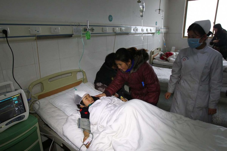 This picture taken on December 16, 2012 shows a nurse and a woman attending to a girl lying on a hospital bed after she was stabbed during a knife attack that took place on December 14 at a primary school in Guangshan county, central China's Henan province. Internet users in China drew comparisons Saturday between violent episodes at schools in China and the U.S. a day after 22 children were stabbed at a Chinese primary school and a U.S. school shooting left 28 dead. (STR/AFP/Getty Images)