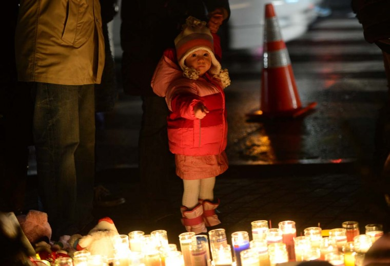 A young child points at candles as people pay their respects at a makeshift shrine to the victims of a elementary school shooting in Newtown, Connecticut, December 16, 2012. A young gunman killed 20 small children and six teachers on December 14, 2012. (Emmanuel Dunande/AFP/Getty Images)