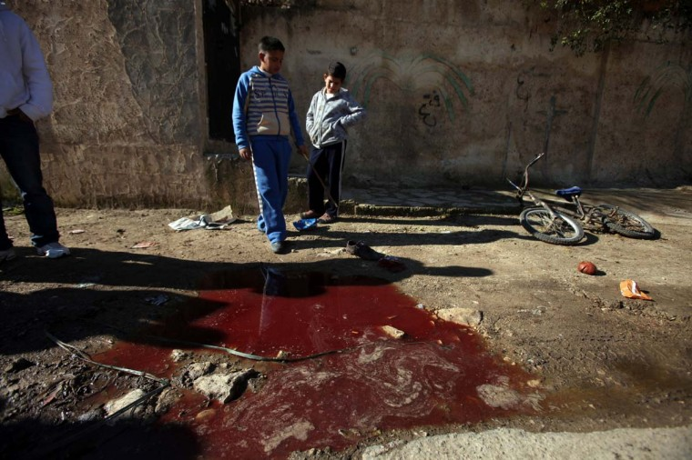 Palestinian children look at blood stains on the ground following a shooting attack in the northern West Bank town of Beit Rima, near Ramallah, on December 17, 2012. Israeli troops arrested four Palestinians on suspicion of shooting offences witnesses told AFP, saying they were accused of shooting at soldiers. (Abbas Momani/AFP/Getty Images)