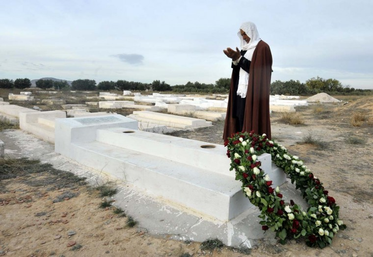 A Tunisian man prays at the mausoleum of Mohamed Bouazizi, the young fruit and vegetable seller whose self-immolation kicked off the Arab Spring in the central town of Sidi Bouzid. Picture taken on December 17, 2012. (Fethi Belaid/AFP/Getty Images)