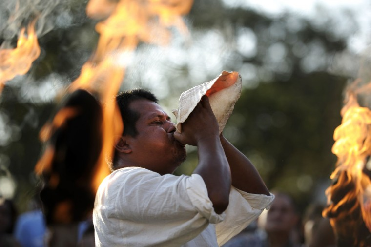 A Mayan shaman blows a seashell during a ceremony in Aguilares, El Salvador, for a celebration of the upcoming end of the Mayan calendar cycle. The conclusion of the 5,125-year Mayan Long Count calendar has been interpreted by some as the beginning of a new Mayan era, and by others as a portent of the apocalypse. (Jose Cabezas/AFP/Getty Images)