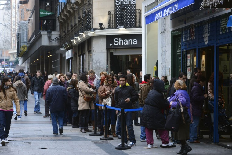 "People queue outside the famous lottery's office, Dona Manolita, to buy the ""Fat One"" (el Gordo) lottery tickets in Madrid on December 18, 2012. On December 22, thousands of lucky ticketholders in Spain could find some relief from the country's economic crisis, as the world's richest lottery will pay out more 2.52 billion euros in prize money. Spain's Christmas lottery named ""El Gordo"" (Fat One) is a Christmas tradition. (Pierre-Philippe Marcou/AFP/Getty Images)"