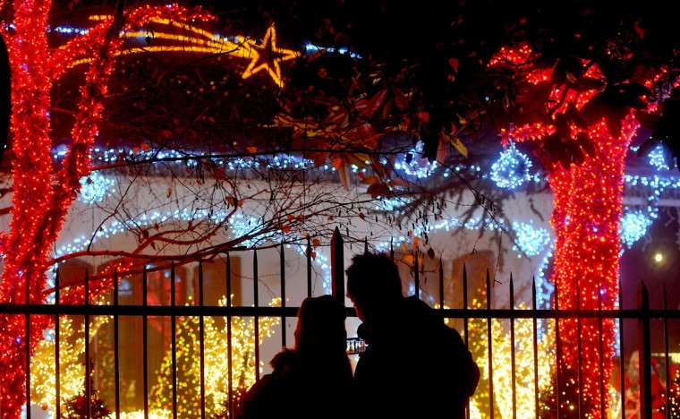 "Visitors take a look at the ""Casa di Babbo Natale"" (Santa's house) illuminated with thousands of lights in Melegnano, Italy, some 25 kilometers from Milan. Massimiliano Goglio, the owner of the house, decorates every year at Christmas. (Tiziana Fabi/AFP/Getty Images)"