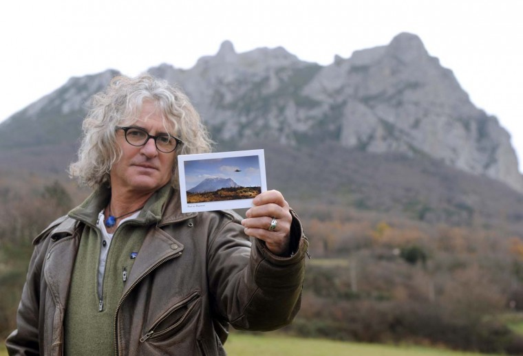 "French photographer Jean-Louis Socquet-Juglard shows the postcard he created, a combo of a flying saucer above the Bugarach peak. The 1,231 meter high peak of Bugarach is one of the few places on Earth some say will be spared when the world reportedly ends on December 21, the end of an era that lasted over 5,000 years, according to the Mayan ""Long Count"" calendar. French authorities have pleaded with New Age fanatics, sightseers and media crews not to converge on the tiny village. Photo taken December 19, 2012. (Eric Cabanis/AFP/Getty Images)"