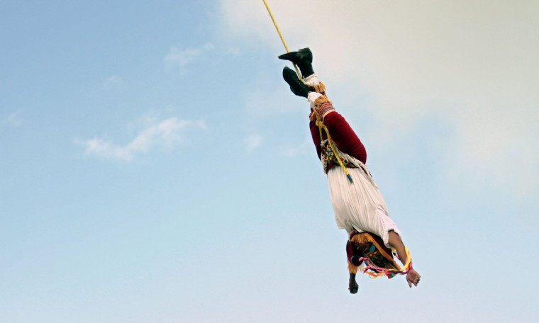 "A Mexican Totonaca native performs the ritual dance of ""Los Voladores"" (The Flyers) at Tulum archaeological park, 130 kilometers south of Cancun, Mexico. Mexico is one of five countries preparing to celebrate on December 21, the end of the Maya Long Count Calendar. (Pedro Pardo/AFP/Getty Images)"