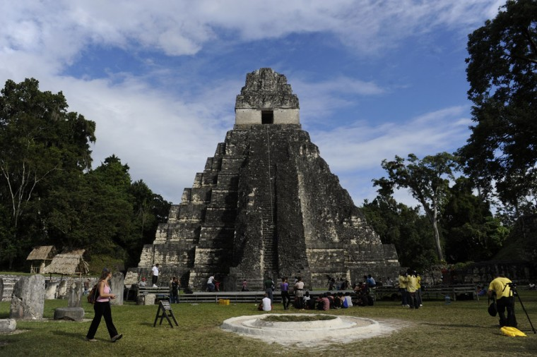 "Tourists are seen in front of the ""Gran Jaguar"" Mayan temple at the Tikal archaeological site, located 560 kilometers north of Guatemala City. Ceremonies will be held at the Tikal site to celebrate the end of the Mayan cycle known as Baktun 13 and the beginning of a new Mayan era. (Johan Ordonez/AFP/Getty Images)"