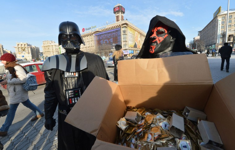 "A leader of the Ukrainian Internet Party, wearing a Darth Vader outfit from the Star Wars saga, and a fellow activist distribute goods in Independence Square in Kiev. The party activists, who traditionally wear Star Wars costumes during their actions, distributed canned foods, matches, condoms, toilet paper, soap, lightbulbs and ""tickets"" for their spacecraft evacuation that will supposedly save Ukrainians from the end of the world on December 21. The date marks the end of the Mayan Long Count calendar, which lasted over 5,000 years. Some believe the date, which coincides with the December solstice, marks the end of the world as foretold by Mayan hieroglyphs -- an idea ridiculed by scholars. (Sergei Supinsky/AFP/Getty Images)"