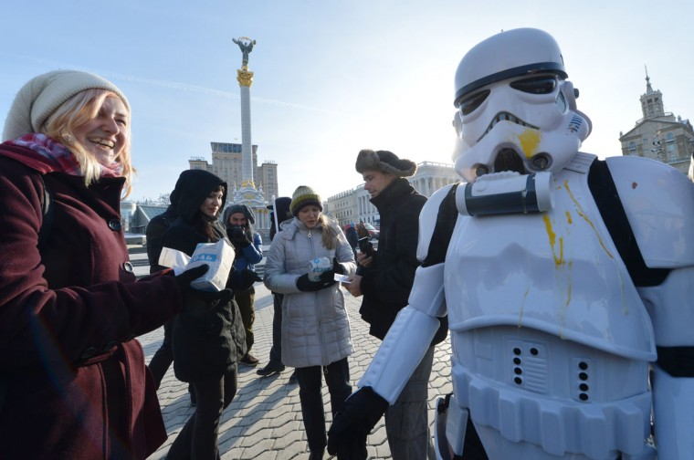 "An activist of the Ukrainian Internet Party, wearing a stormtrooper outfit from the Star Wars saga, distributes goods in Independence Square in Kiev on December 20. The party activists, who traditionally wear Star Wars costumes during their actions, distributed canned foods, matches, condoms, toilet paper, soap, lightbulbs and ""tickets"" for their spacecraft evacuation that will supposedly save Ukrainians from the end of the world on December 21. The date marks the end of the Mayan Long Count calendar, which lasted over 5,000 years. Some believe the date, which coincides with the December solstice, marks the end of the world as foretold by Mayan hieroglyphs -- an idea ridiculed by scholars. (Sergei Supinsky/AFP/Getty Images)"