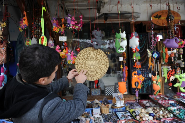 A tourist looks at products on sale on the streets of Sirince, a small village in western Turkey on December 20, 2012. Believers in doomsday predictions are flocking to Sirinice, which some believe is the only safe haven from the rumored Mayan-predicted apocalypse since the Virgin Mary is said to have risen to heaven from there. (Bulent Kilic/AFP/Getty Images)