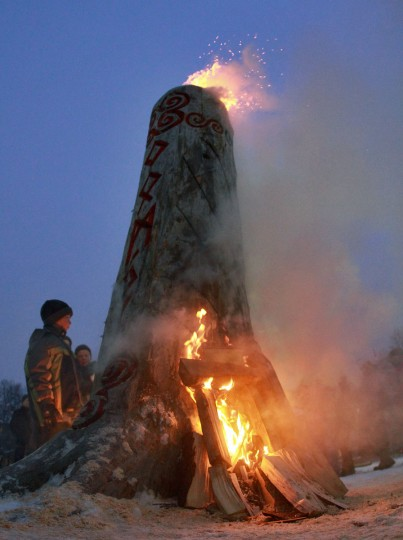 A boy participates in winter solstice celebrations to complete the Christmas 'Blukis' (stump) burning ceremony at Lukiskes Square in Vilnius, Lithuania on December 21, 2012. In pagan traditions in Lithuania exists a popular myth of stealing and conquering the sun. To free the Sun, the Blukis is dragged around a town, beat and later burned. (Petras Malukas/AFP/Getty Images)