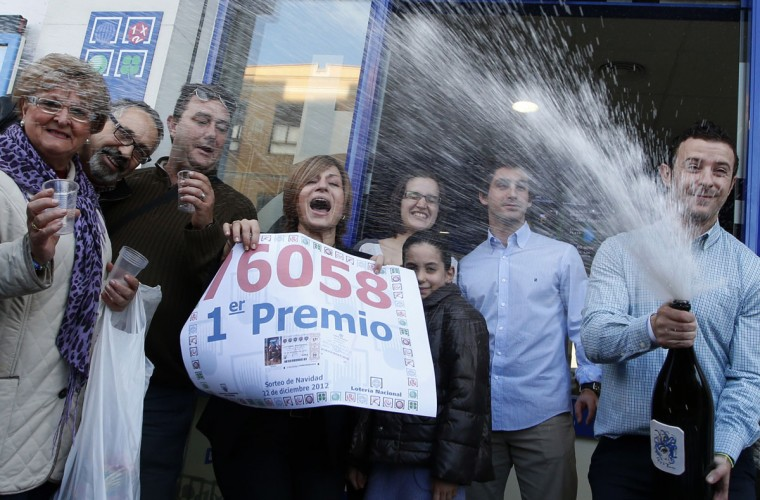 "People celebrate after winning the first prize of Spain's Christmas lottery, named ""El Gordo"" (Fat One), in Grañén, in Alaquas, near Valencia, on December 22, 2012. The world's richest lottery showered prizes of up to 2.5 billion euros ($3.3 billion) on crisis-hit Spaniards in an annual draw of the ""El Gordo"" or ""The Fat One"". The jackpot went to number 76058, which is split into a total of 1,800 ""decimo"" tickets each paying out 400,000 euros. (Jose Jordan/AFP/Getty Images)"
