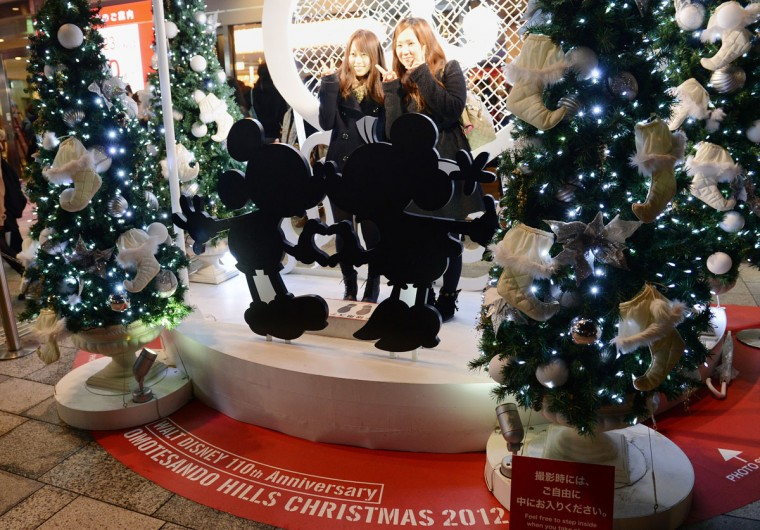 Christmas shoppers pose for a picture next to a Mickey and Minnie Mouse light display outside a shopping mall in Tokyo. Although Christians only account for around only one percent of Japan's population, people usually celebrate the holiday by spending time with their sweethearts and exchanging gifts. (Toshifumi Kitamura/AFP/Getty Images)
