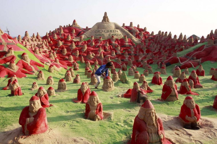 Indian Sand artist Sudersan Pattnaik works on a sand sculpture with over 500 Santa Claus statues at Golden Beach in Puri on about 65 kilometres away from Bhubaneswar on December 22, 2012. (STR/AFP/Getty Images)