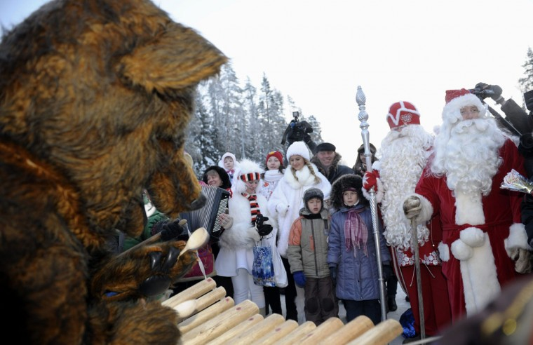 Bear Miska, left, plays xylophone on the occasion of a symbolic meeting of Snow Maiden, Father Frost and Santa Claus at the Nuijamaa border station between Finland and Russia in Lappeenranta, Finland, on December 23, 2012. (Heikki Saukkomaa/AFP/Getty Images)