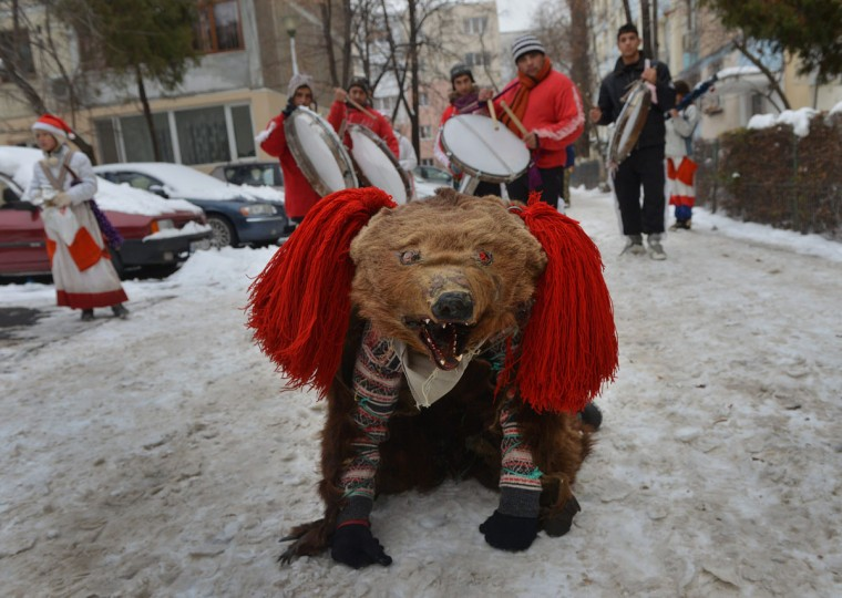 Romanian children wearing real bear skins coming from the Bacau region (some 340 km northeast from Bucharest) perform the bears' dance, an ancient tradition before Christmas, in Bucharest, December 23, 2012. Such ceremonies are still popular in the Balkans and Romania, especially during the days between Christmas Eve to Epiphany. Originally, they were ceremonies related to the periodic return of the dead, with people wearing all sorts of masks and behaving like animals such as horses, goats or bears. It is believed that bears banish demons from houses and farmyards and wish inhabitants a happy year. (Daniel Mihailescu/AFP/Getty Images)