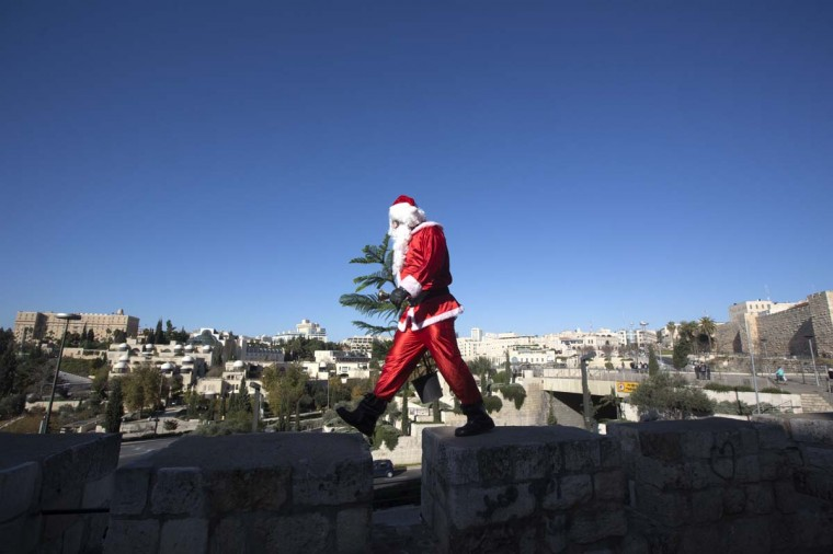 A Palestinian man dressed up as Santa Claus carries a Christmas tree and rings a bell as he walks along the wall of Jerusalem's Old City, on December 23 2012, as Christians around the world prepare for Christmas celebrations. (Menahem Kahana/AFP/Getty Images)