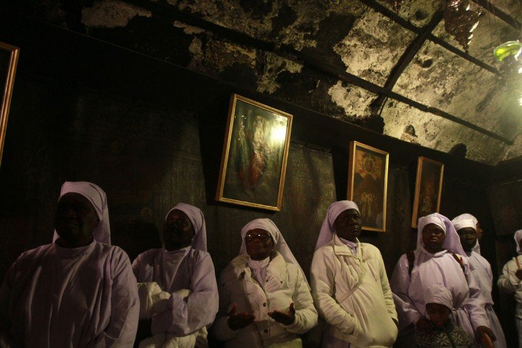 Nigerian Christian pilgrims pray inside the Grotto at the Church of the Nativity in the biblical West Bank city of Bethlehem, believed to be the birthplace of Jesus Christ, on December 24, 2012. Thousands of Palestinians and tourists were flocking to Bethlehem to mark Christmas at the site where many believe Jesus Christ was born. (Musa Al-Shaer/AFP/Getty Images)