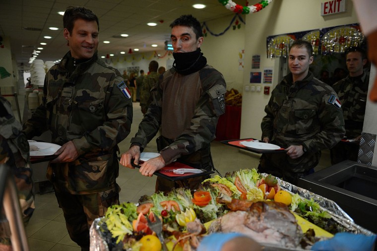French soldiers with the NATO-led International Security Assistance Force (ISAF) lineup to take their food during a special meal on Christmas Day at Kabul International Airport on December 25, 2012. There are presently around 100,000 US-led NATO troops fighting a decade-long Taliban led insurgency in Afghanistan. (Shah Marai/AFP/Getty Images)