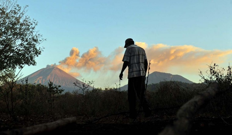 A man walks in the surroundings of the San Cristobal volcano (background L) in Chonco, Chinandega, on December 26, 2012. The San Cristobal volcano began spewing smoke and ashes on the eve. (Hector Retamal/AFP/Getty Images)