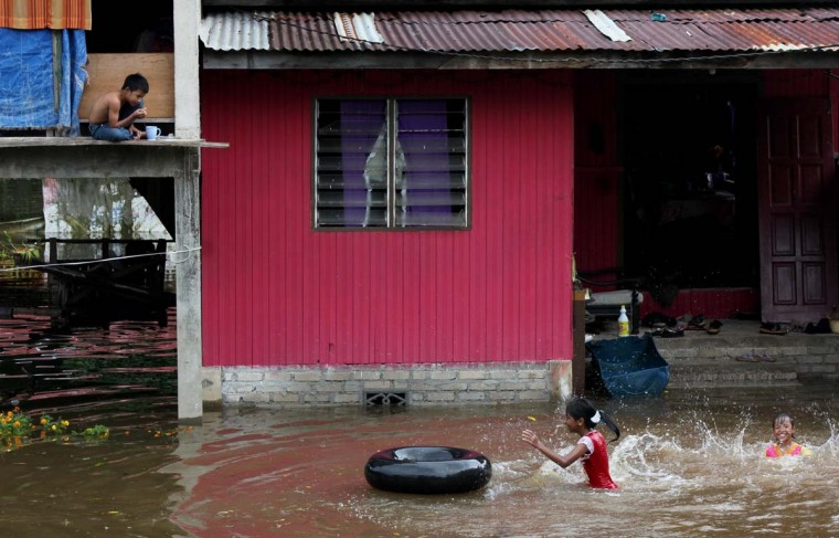 This picture taken on December 26, 2012 shows children playing in flood waters outside their home in Malaysia's northeastern town of Rantau Panjang, boardering Thailand. Floods triggered by torrential monsoon rains in Malaysia have claimed the life of a second victim although waters have subsided, allowing some evacuees to return home from relief centres, reports said. (STR/AFP/Getty Images)