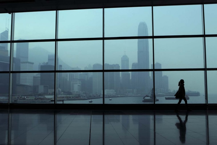 A woman walks past a tinted window in front of the city skyline in Hong Kong on December 27, 2012. With the global economic weakness continuing to impact domestic economy, the IMF said it expects Hong Kong's economy to grow 1.25 percent this year, before rebounding to three percent next year. (Dale de la Rey/AFP/Getty Images)