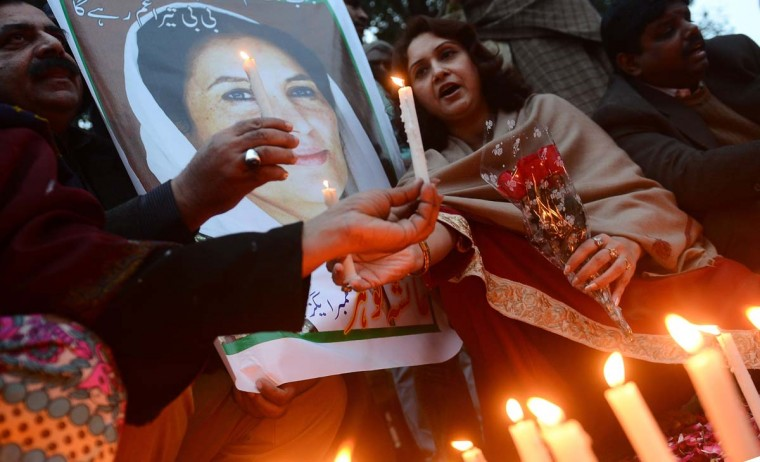 Activists of ruling Pakistan People's Party (PPP) hold a portrait of the late former Pakistan premier Benazir Bhutto during a candlelight ceremony in Lahore on December 27, 2012, on the fifth anniversary of her assassination. Vast crowds gathered to mark the fifth anniversary of the assassination of former Pakistan premier Benazir Bhutto, and to witness her son launch his own political career. (Arif ALIArif Ali/AFP/Getty Images)