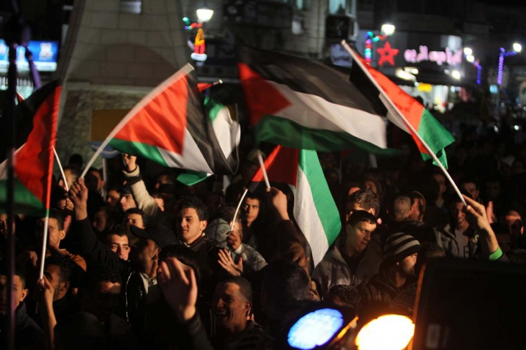 Palestinians wave their flag as they celebrate on new year's eve in the West Bank city of Ramallah on December 31, 2012. (Abbas Momani/AFP/Getty Images)