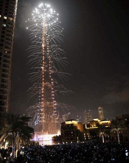 Revellers watch fireworks illuminating over Burj Khalifa in Dubai on January 1, 2013. Thousands of people gathered to celebrate the New Year at midnight. (STR/AFP/Getty Images)