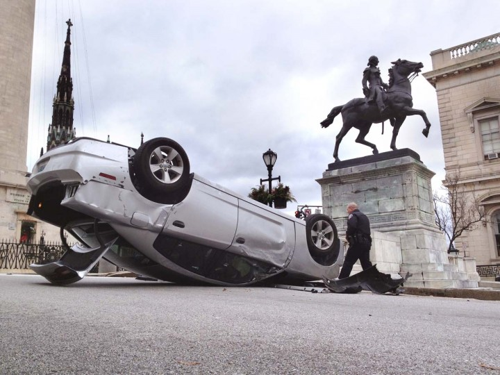 A Baltimore City Police Officer walks by a flipped car after an accident on Mt. Vernon Dec. 27. (Lloyd Fox/Baltimore Sun)
