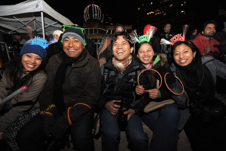 Puja Sthapit, (c) 28; Anit Lacoul, 29; Yogen Joshi, 31; Prashna Joshi, 29; and Deena Shakya, 28. New Year's revelers listen to the band Outbreak at the Inner Harbor. (Algerina Perna/Baltimore Sun)