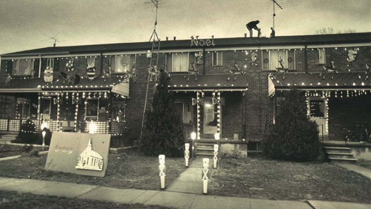 Residents of the 1100 block of Boxwood Lane in the Essex area have cooperated in setting up a Christmas display that has a Santa and his reindeer spanning five porch tops. Vernon Church adjusts the Nativity scene on the roof on one house in the block. Dec. 22, 1971. (Richard Childress/Baltimore Sun)