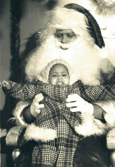 Charmaine Simms, 2, got a little frightened by a heavy Ho! Ho! Ho! from Santa Claus at the Sears department store on North Avenue. Dec. 1, 1976. (Lloyd Pearson/Baltimore Sun)