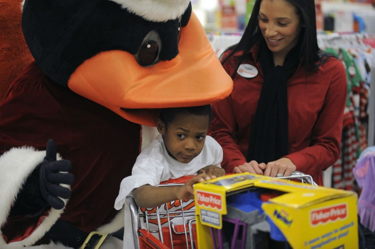 Nov. 30: Oriole snack: On a shopping spree hosted by Baltimore Orioles center fielder Adam Jones, Jeremiah Harris, 5 reacts as the Orioles Bird puts his beak over his head during shopping for two families at a Target shopping center Thursday, Nov. 29, 2012. Jones, who recently garnered a second Gold Glove award, treated the families through OriolesREACH, to a round of shopping for toys and clothing. (Karl Merton Ferron/Baltimore Sun)
