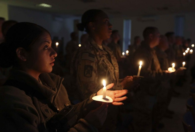 U.S. troops from the NATO-led International Security Assistance Force (ISAF) hold candles during a mass at a NATO camp on Christmas Eve in Kabul on December 24, 2012. (Omar Sobhani/Reuters)