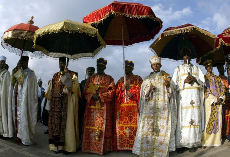 "Ethiopian orthodox priests in their satin robes stand under sequined velvet umbrellas during the annual Epiphany celebrations, called ""Timket"", of the Ethiopian Orthodox Church in Addis Ababa on January 20, 2004. ""Timket"", the greatest Ethiopian festival of the year, commemorates the baptisom of Jesus in the Jordan River by John the Baptist. (Wolfgang Rattay/Reuters)"