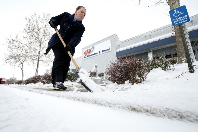 Amy Freemire shovels the sidewalk outside of work at AAA Insurance and Travel offices, 10600 Metcalf Avenue, during snowstorm in Overland Park, Kansas. (John Sleezer/Kansas City Star/MCT)
