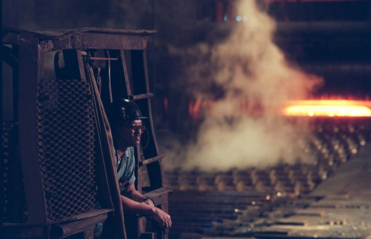 "AUGUST 20, 1995: In the plate mill area of Bethlehem Steel plant, where over 5,000 are presently employed, Douglas Penn, age 56, works as a ""Heater,"" and photographed here in the charging crane, with thje ""3 High Mill"" behind him. Penn, who has worked at Beth Steel for 36 years, said, ""I take cold slabs, put 'em into burners and heat 'em up. You get accustomed to the heat. If the outside temperature is 100 degrees, its 150 degrees in here. "" (Amy Davis/Baltimore Sun)"