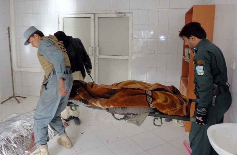 Afghan policemen carry the dead body of a victim at a local hospital after a suicide bomb attack in Khost province December 26, 2012. A suicide bomber killed three people in an attack on a U.S. base in Afghanistan on Wednesday, the same base that is believed to be used by the CIA and which a suicide bomber attacked three years ago killing seven CIA employees. (Anwarullah/Reuters)