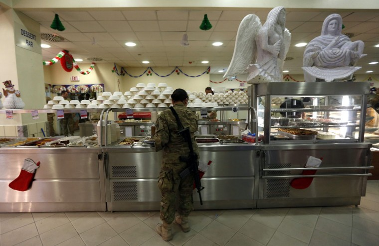 A NATO troop from the International Security Assistance Force (ISAF) gets food on Christmas in Kabul on December 25, 2012. (Mohammad Ismail/Reuters)