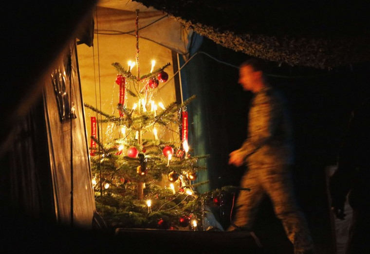 A German Bundeswehr army soldier walks to his tent, passing a Christmas tree, at the combat outpost OP North, near Baghlan, in northern Afghanistan, on December 9, 2012. The soldiers are celebrating their last Christmas at the combat outpost this year before it is removed in 2013. (Fabrizio Bensch/Reuters)