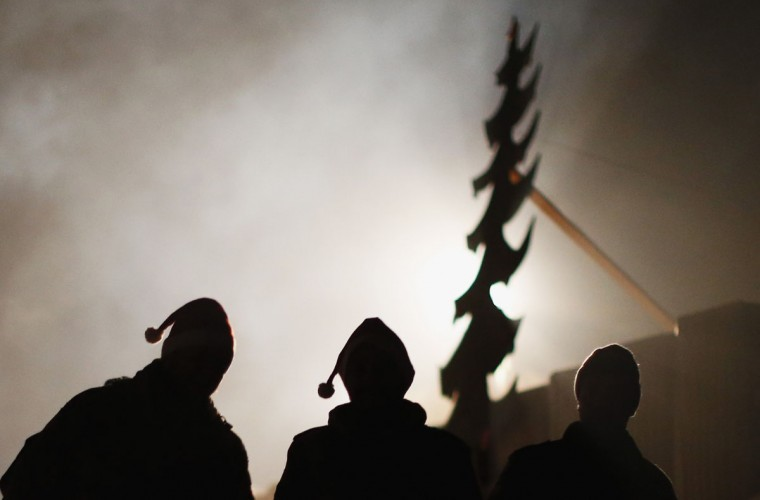 German Bundeswehr army soldiers are silhouetted as they leave a Christmas market in their combat outpost OP North, near Baghlan, in northern Afghanistan, on December 9, 2012. The soldiers are celebrating their last Christmas at the combat outpost this year before it is removed in 2013. (Fabrizio Bensch/Reuters)