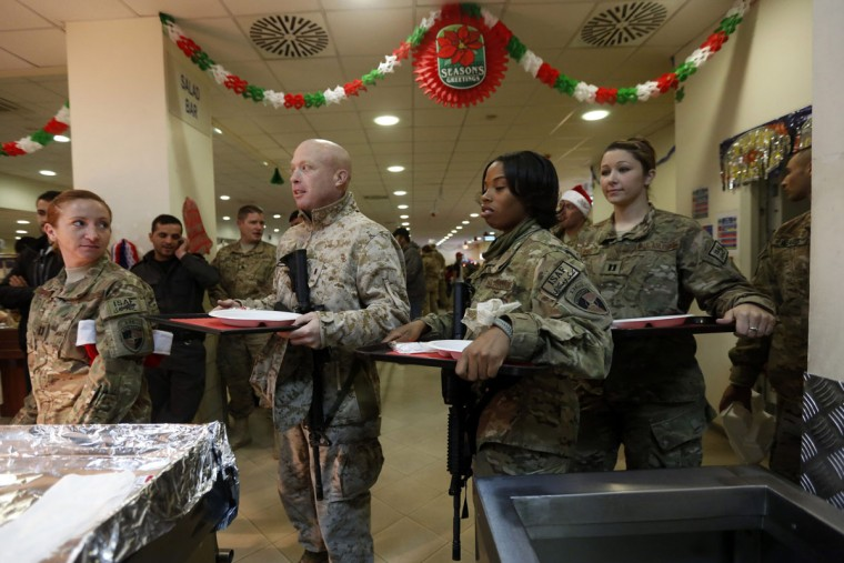 NATO troops from the International Security Assistance Force (ISAF) get food on Christmas in Kabul on December 25, 2012. (Mohammad Ismail/Reuters)