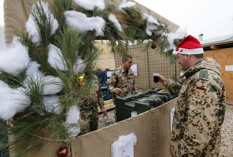 A German Bundeswehr army soldier gets a hot drink in a Christmas market at their combat outpost OP North, near Baghlan, northern Afghanistan on December 9, 2012. The soldiers are celebrating their last Christmas at the combat outpost this year before it is removed in 2013. (Fabrizio Bensch/Reuters)